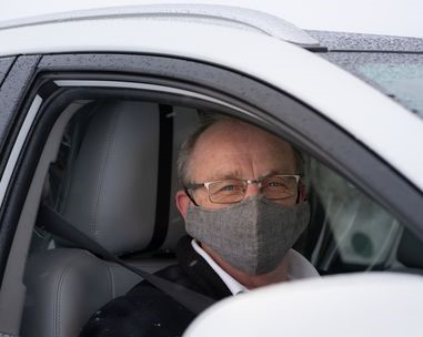 covid taxis hexham - ecocabs driver wearing a grey face mask at the wheel of a white taxi